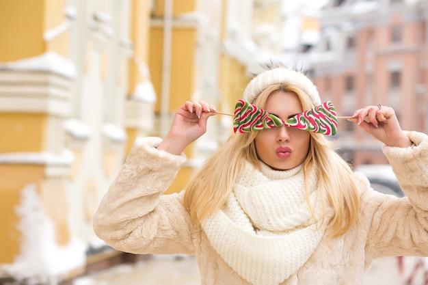 Glamoureus blond model met lang haar met een warme gebreide muts en heerlijke kerstsnoepjes in de buurt van haar gezicht