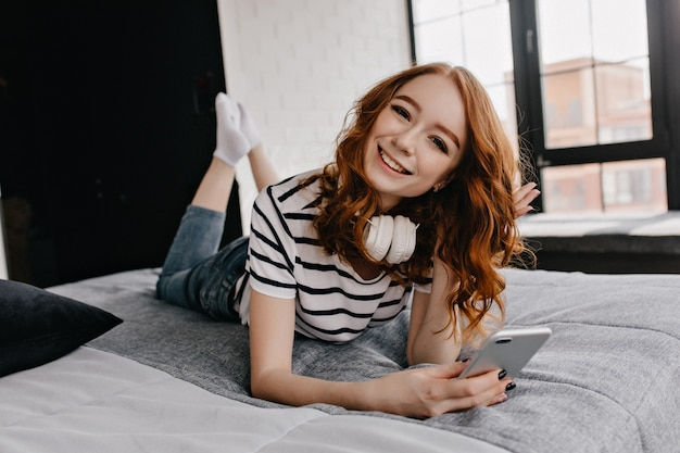 Glamoureus europees meisje met behulp van telefoon terwijl poseren op bed. goedgehumeurde gembervrouw in hoofdtelefoons die pret in weekend hebben.