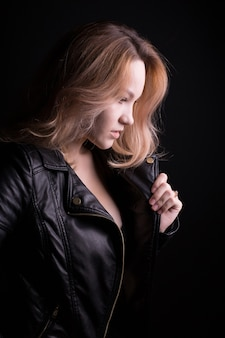 Glamoureus jong model met weelderig golvend haar, draagt een leren jas en poseert op een zwarte achtergrond