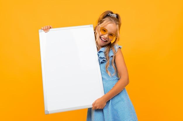 Glamoureus meisje met een wit bord op een gele muur