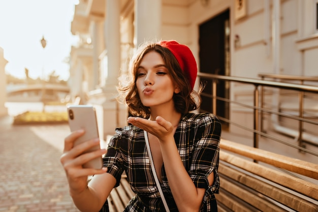 Glamoureuze brunette vrouw lucht kus verzenden tijdens het maken van selfie in zonnige dag. sierlijk frans vrouwelijk model dat smartphone houdt en een foto van zichzelf neemt.