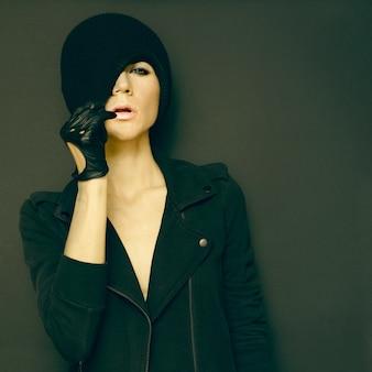 Glamoureuze dame op zwarte achtergrond in trendy handschoenen en hoed herfst mode-stijl
