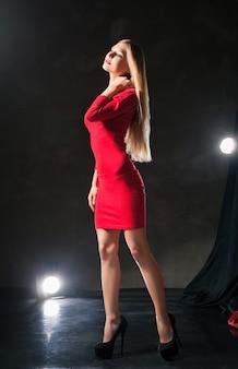 Glamoureuze dromerige jonge vrouw die een rode jurk draagt die op het podium staat en haar nek aanraakt.