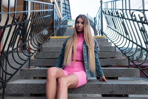 Glamoureuze europese jonge vrouw blonde in een vintage blauw denim jasje in stijlvolle roze korte broek in een trendy roze top zit op een stenen trap in de stad. modieus mooi meisje. retro stijl. zomer.
