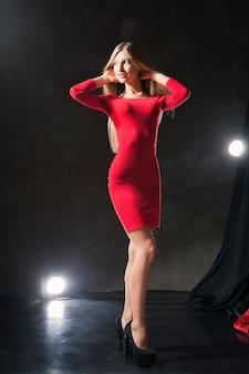 Glamoureuze glimlachende jonge vrouw die een rode jurk draagt die op het podium staat en haar nek aanraakt.