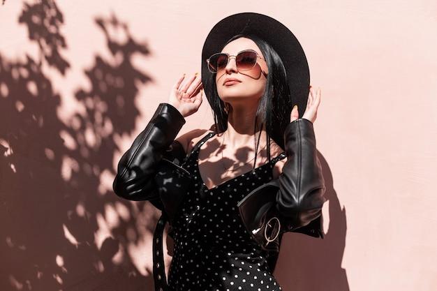 Glamoureuze jonge brunette vrouw in mooie modieuze zwarte kleding maakt hoed buitenshuis recht. luxe sexy meisje in jurk in leren jas in zonnebril poseren en geniet van zonlicht. zomerse stijl.