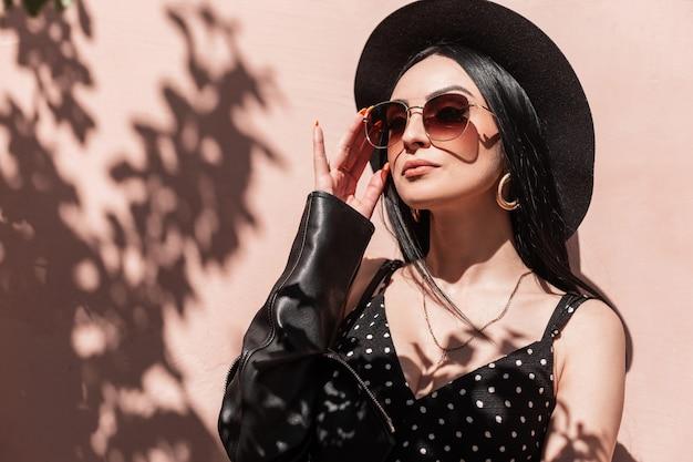 Glamoureuze jonge brunette vrouw in mooie modieuze zwarte kleding maakt zonnebril buitenshuis recht. mooie sexy meisje in jurk in leren jas in hoed poseren en geniet van zonlicht. zomer mode.
