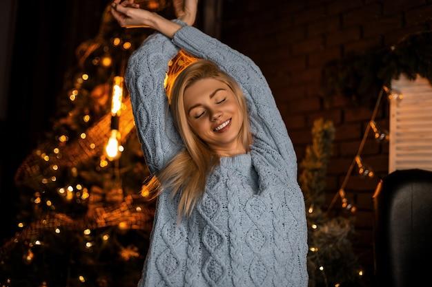 Glamoureuze jonge vrouw in een modieus gebreid blauw pak met blond haar poseren met gesloten ogen in een kamer met een kerstboom