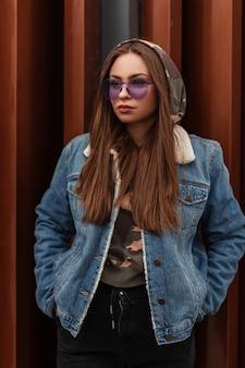 Glamoureuze mooie jonge hipster vrouw in trendy paarse bril in oversized spijkerjasje met lang haar is rust in de buurt van metalen muur in de stad. modern stedelijk meisjesmodel in stijlvolle kleding buitenshuis
