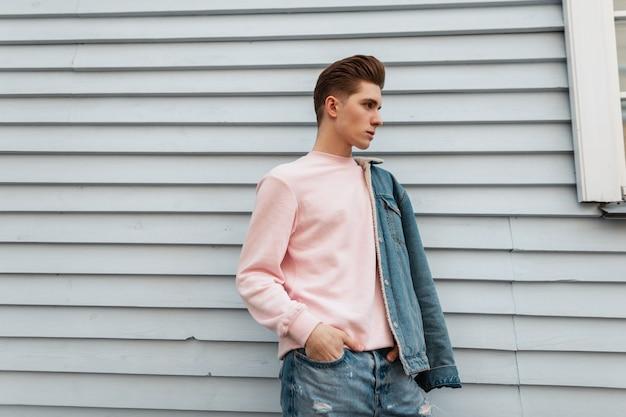 Glamoureuze mooie jonge man model in trendy roze sweatshirt in mode denim blauwe jeugd kleding poseren in de buurt van witte muur buitenshuis. stedelijke man in jeans vrijetijdskleding uit nieuwe collectie poses op straat.