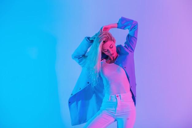 Glamoureuze stijlvolle jonge blonde vrouw model in modieus pak met blauwe blazer met witte jeans poses op heldere pastelkleurige neon roze lichten in studio