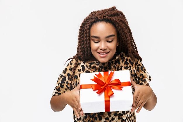 Glamoureuze vrouw die lacht en de huidige doos met strik vasthoudt terwijl ze geïsoleerd tegen een witte muur staat