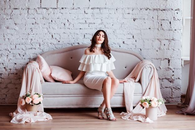 Glamoureuze vrouw gekleed in witte jurk zit op de bank versierd met roze kussens