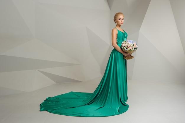Glamoureuze vrouw in een groene jurk met blond haar houdt een boeket