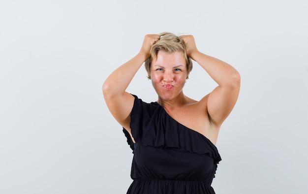 Glamoureuze vrouw in zwarte blouse poseren met handen op het hoofd terwijl lippen pruilen en zelfverzekerd op zoek