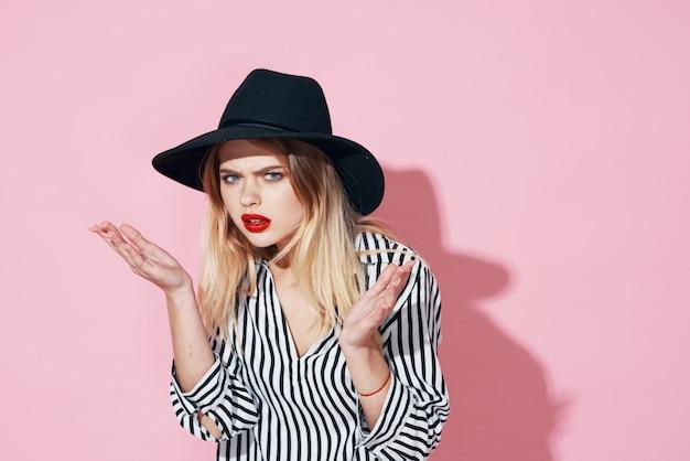 Glamoureuze vrouw in zwarte hoed en gestreept shirt lichte make-up roze achtergrond