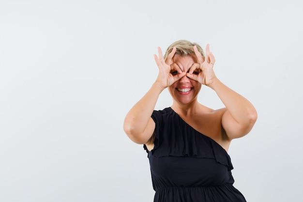 Glamoureuze vrouw verrekijker gebaar maken in zwarte blouse en op zoek ontspannen. vooraanzicht.