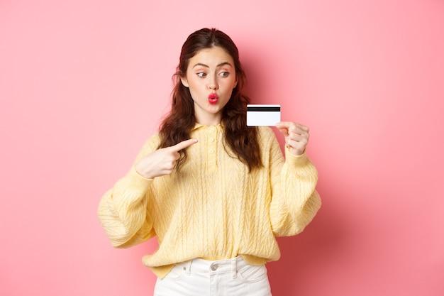 Glamourmeisje gaat winkelen, kijkt opgewonden en wijst naar plastic creditcard, staande tegen roze muur.