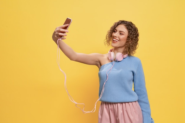 Glamourmeisje met hoofdtelefoons selfie doen, gebruikend telefoon.