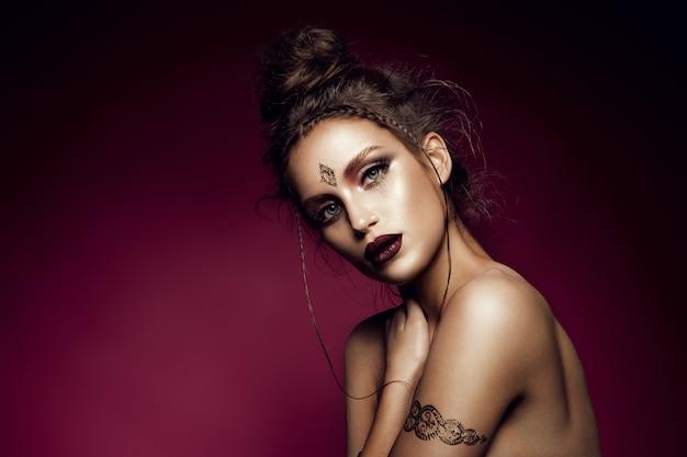 Glamourportret van mooi vrouwenmodel met gouden make-up en romantisch kapsel.