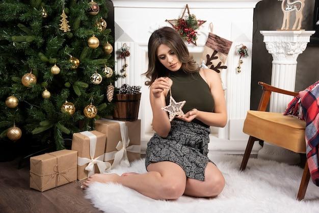 Glamourvrouw in zwarte bovenkant die op wit tapijt zit en houten ster toont