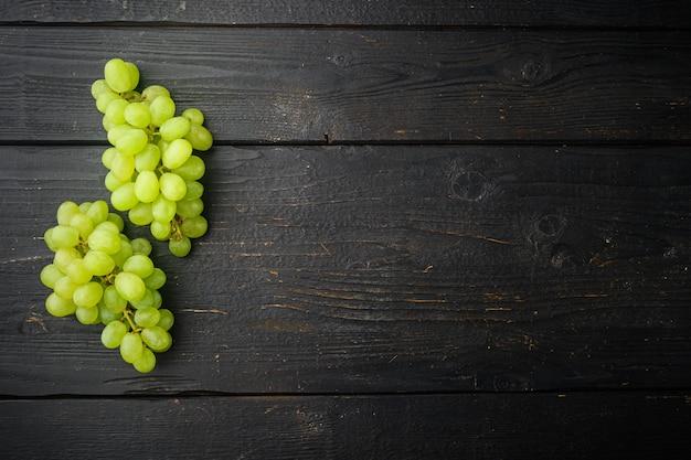 Glans druivenfruit set, groen fruit, op zwarte houten tafel, bovenaanzicht plat lag