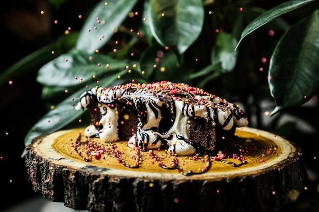 Glans het gieten op chocoladecake op het houten zijaanzicht van de raads syrop