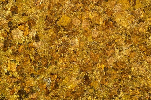Glanzend geel bladgoud of resten van gouden folietextuur als achtergrond