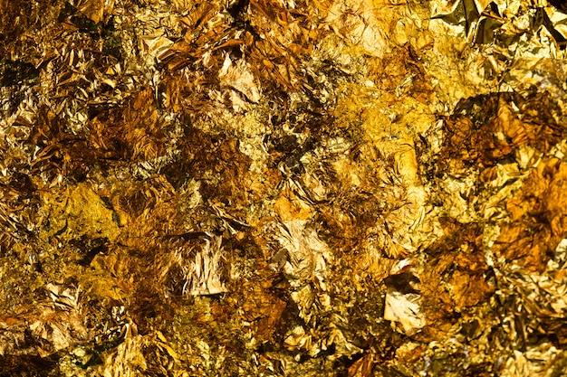 Glanzend geel bladgoud of restjes goudfolie achtergrond