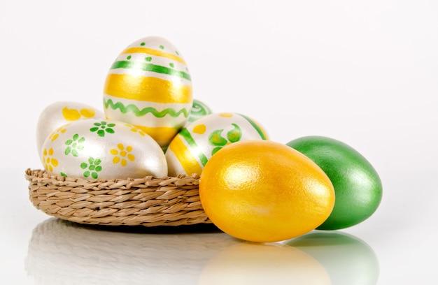 Glanzend geel en groen paaseieren op wit