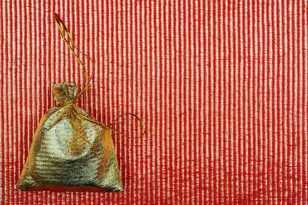 Glanzend gouden zakje op rood