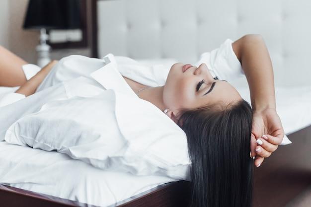 Glanzend haar portret van een mooi gelukkig brunette meisje in bed op haar rug.