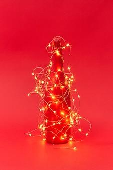 Glanzend kerstverlichtingskoord op een creatief geschilderde wijnfles op een rode achtergrond met kopieerruimte. nieuwjaar felicitatiekaart.