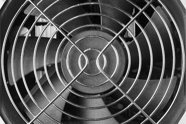 Glanzend metalen gaas over een plastic ventilator.
