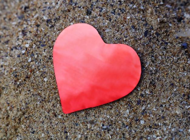 Glanzend rood document hart op het zand