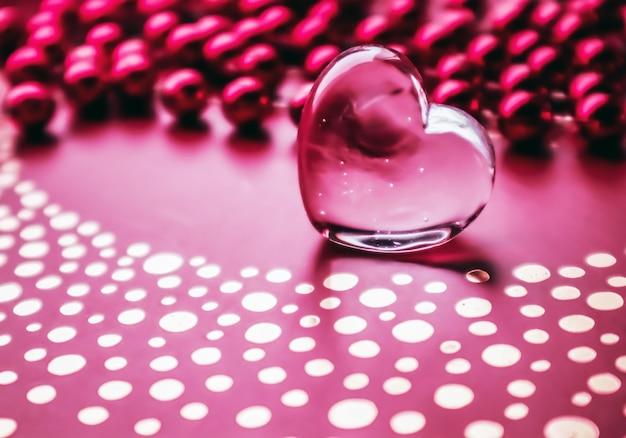 Glanzend transparant hart en een groep rode kralen perfecte valentijnsdag wenskaart achtergrond
