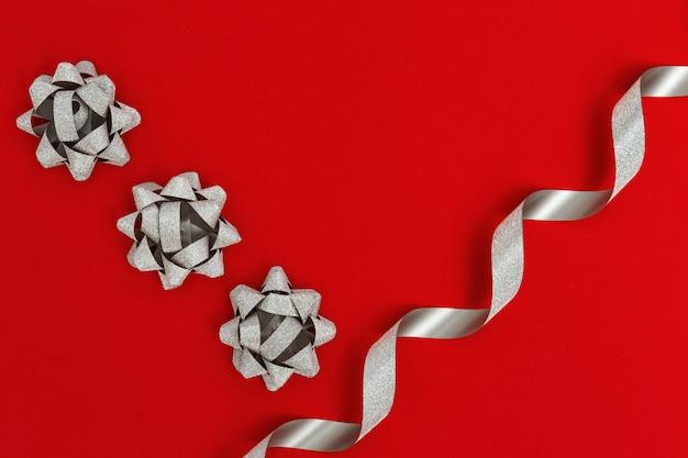 Glanzend zilveren lint en strik op rode papier achtergrond. feestelijke decoratie. cristmas decor. kopieer ruimte. plat leggen.