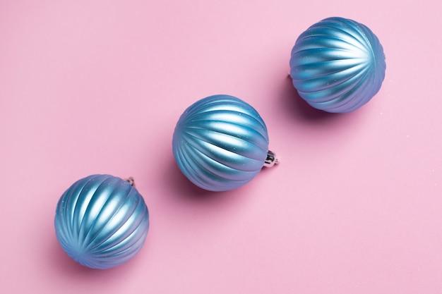Glanzende blauwe ballen op een roze achtergrond voor kerstversiering