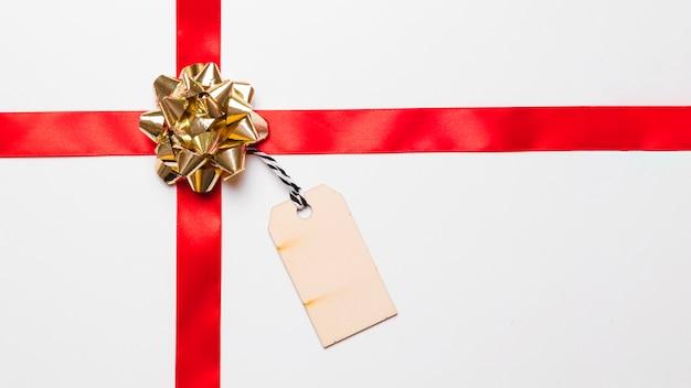 Glanzende geschenkboog met zijden lint en tag