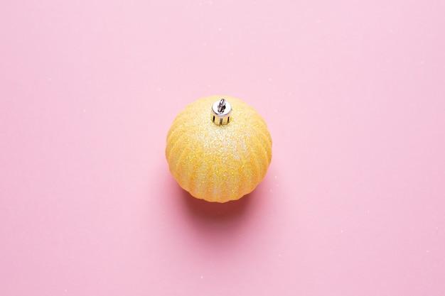 Glanzende gouden bal op een roze achtergrond, bovenaanzicht van kerstversiering Premium Foto