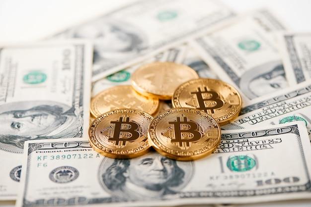 Glanzende gouden bitcoins die op honderd dollarsrekeningen liggen die de grootste cryptocurrency presenteren en een nieuwe futuristische vorm van geld.