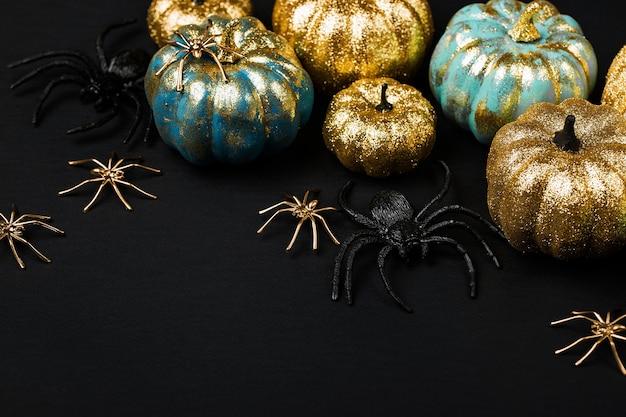 Glanzende gouden en blauwe pompoenen met spinnen. halloween-versieringen. trendy vakantieconcept.