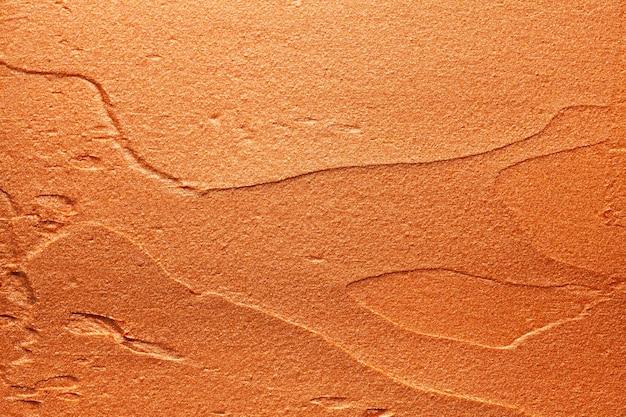 Glanzende gouden oranje lippenstift achtergrondstructuur vlekkerig