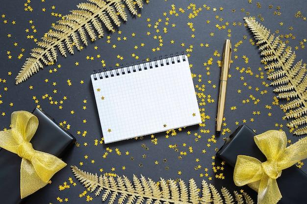 Glanzende gouden varenbladeren en geschenkdozen op een zwarte achtergrond met glitter gouden sterren, open spiraal kladblok en pen