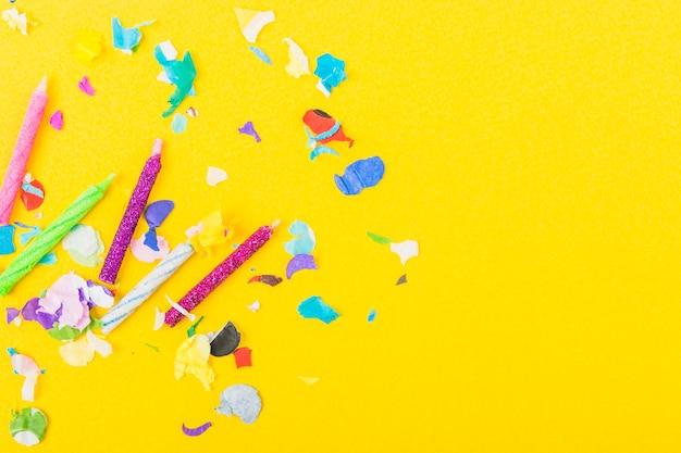 Glanzende kaarsen en confetti op de gele achtergrond