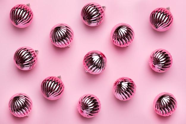 Glanzende kerstballen voor decoratie op roze achtergrond, nieuwjaar patroon bovenaanzicht
