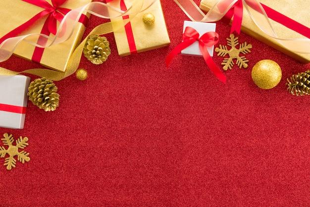 Glanzende kerstmis en nieuwjaar vakantie geschenkdozen met het verfraaien van items op kleurrijke rode glinsterende achtergrond