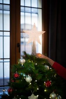 Glanzende kerstmisster van de close-up bovenop boom
