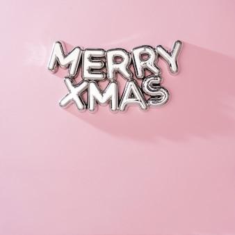 Glanzende merry xmas kerstboomdecoratie met roze achtergrond. minimaal concept van de vakantie van het nieuwe jaarfeest. plat leggen.
