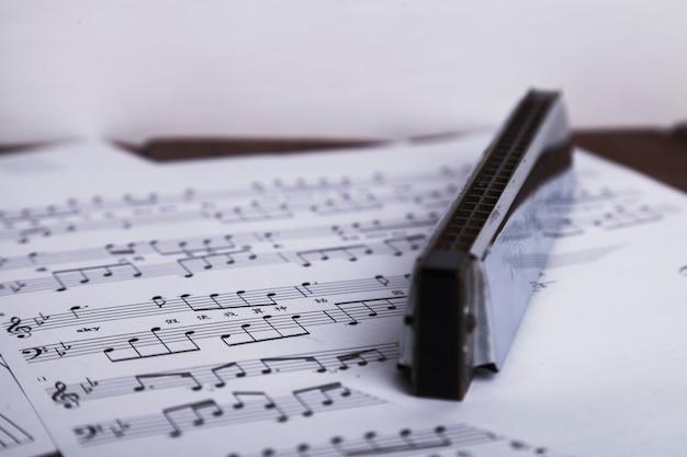 Glanzende mondharmonica op bladmuziek